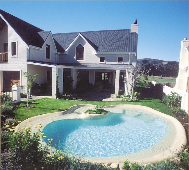 Grass is a natural approach and is appropriate with a beach pool.
